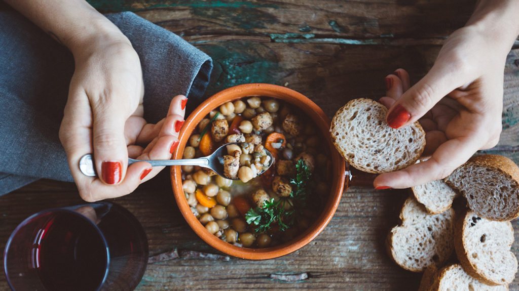 a woman eating a bowl of beans and bread as that is how to stop hair loss