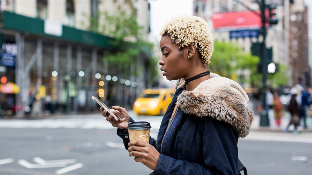 a woman walking on a street and looking at her phone as she looks up if Hepatitis C outside the body