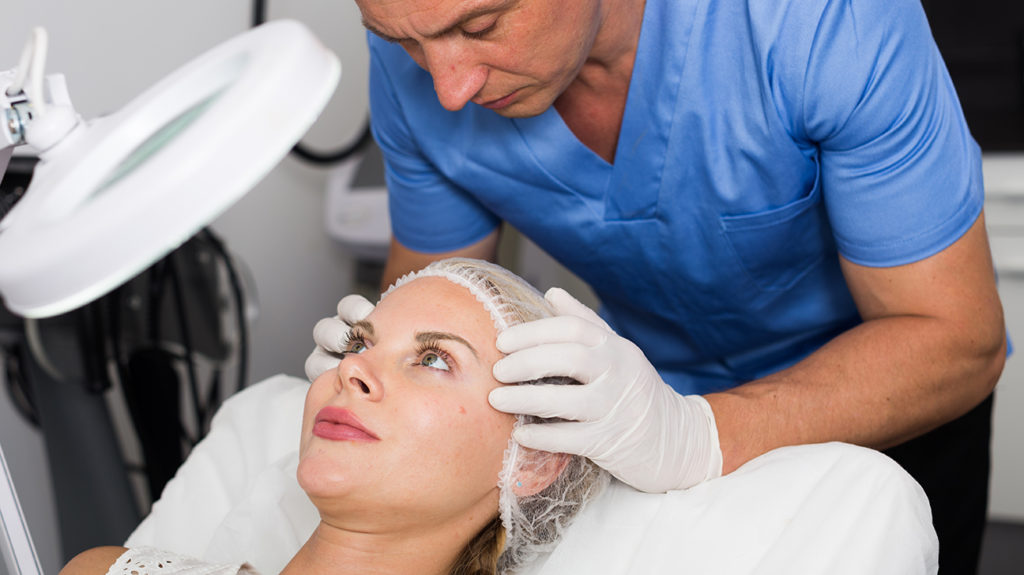 a man examining a woman's face before a dermaplaning procedure