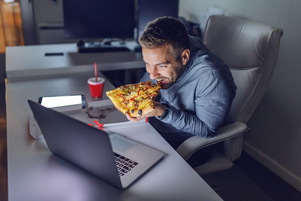 Man eating pizza at night