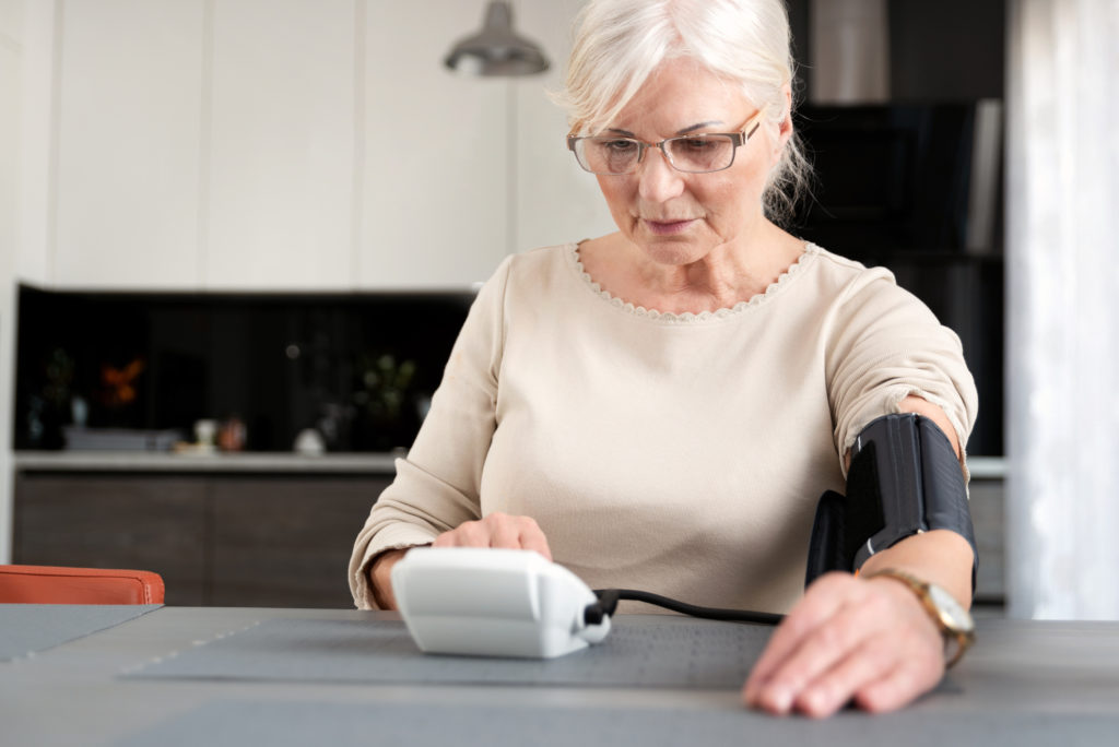 Woman checking her blood pressure at home