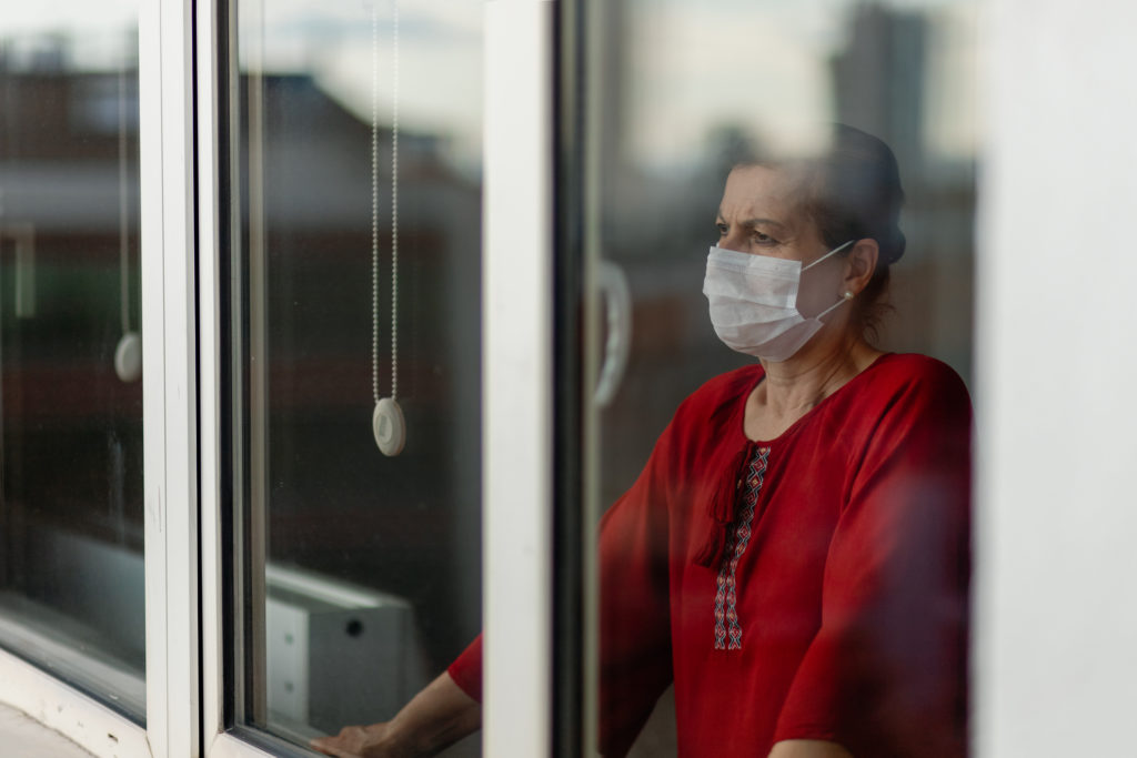 Woman wearing face mask looking out of a window