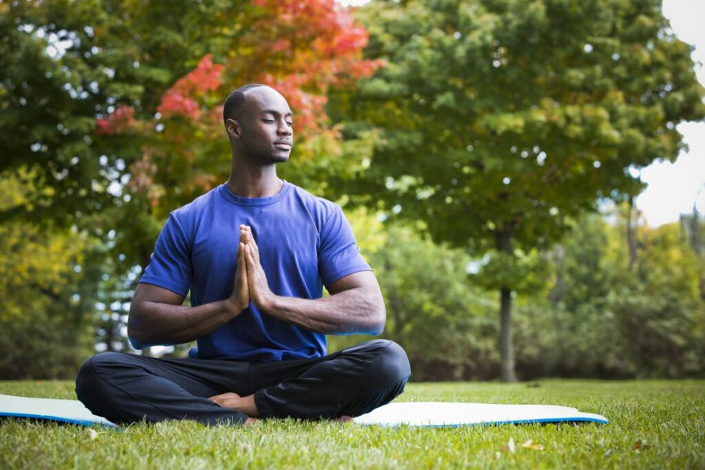man doing yoga in the park