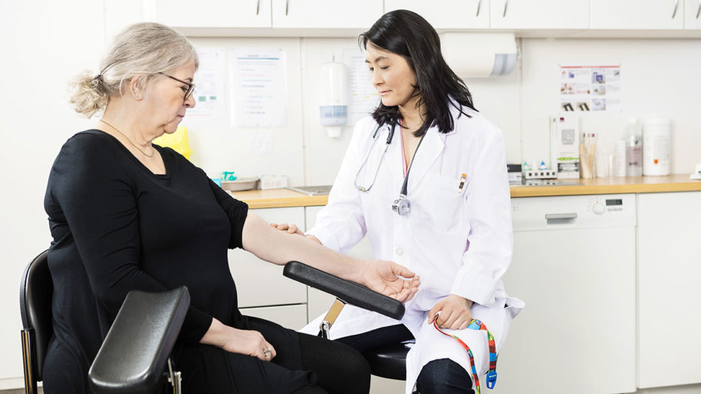A doctor looks for the vein on a patient's arm after first discussing with the patient does medicare cover blood tests.