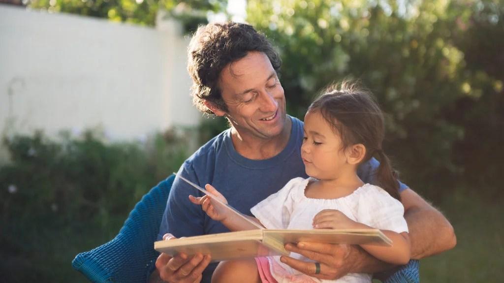 Pai e filha lendo no jardim