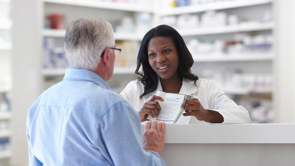 a senior man talking to a pharmacist about medicare part d deductible for 2020