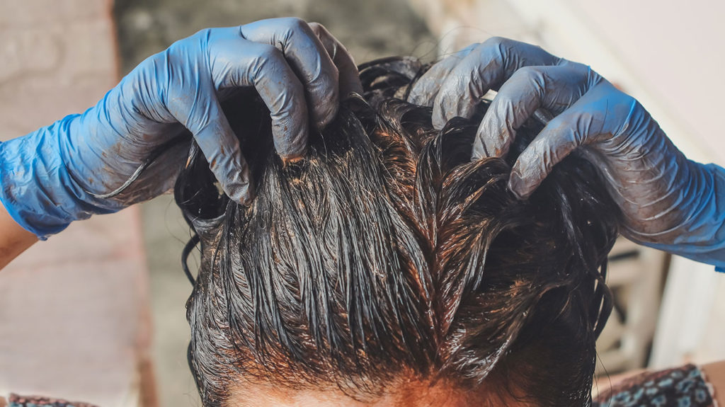 A woman dyes her hair with henna, a natural hair dye.
