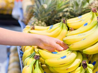 A person picks up bananas, which are a food for an upset stomach.