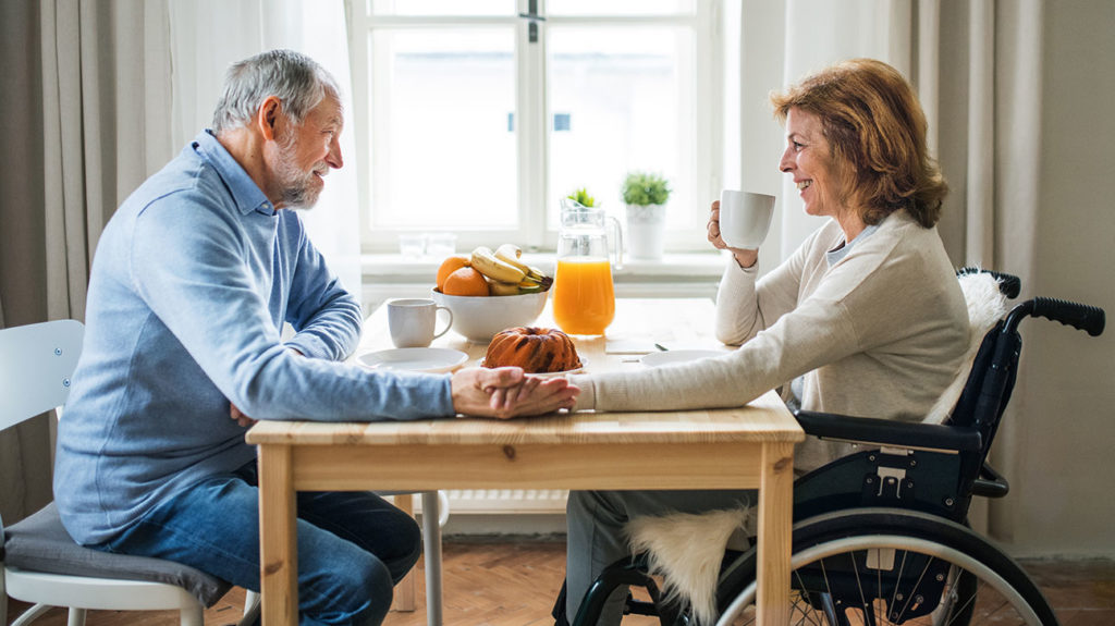A couple who pay for the cost of medicare plan g sit together for breakfast.
