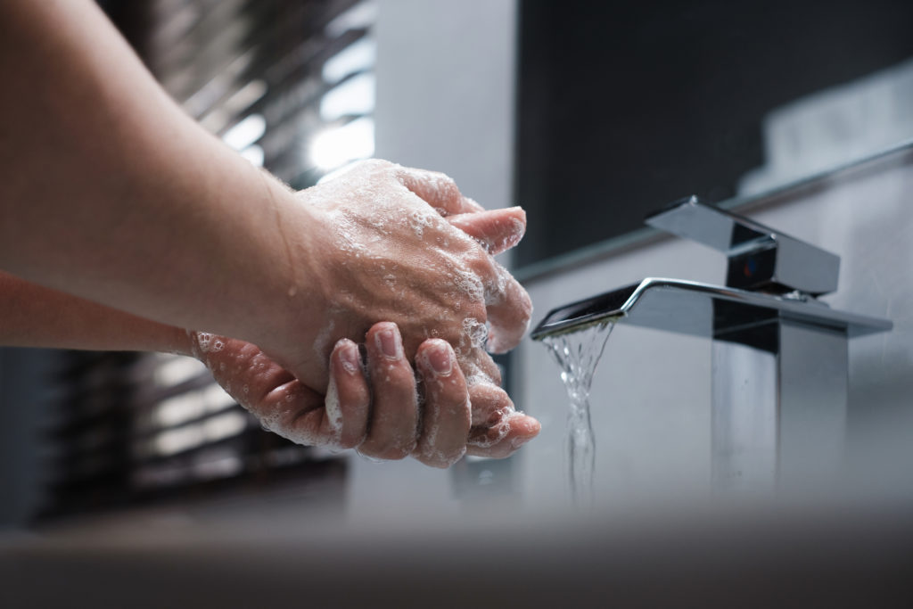 person washing their hands at the sink