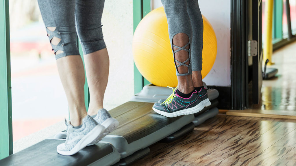 Two women at the gym do calf raises as one of the remedies for restless leg syndrome.