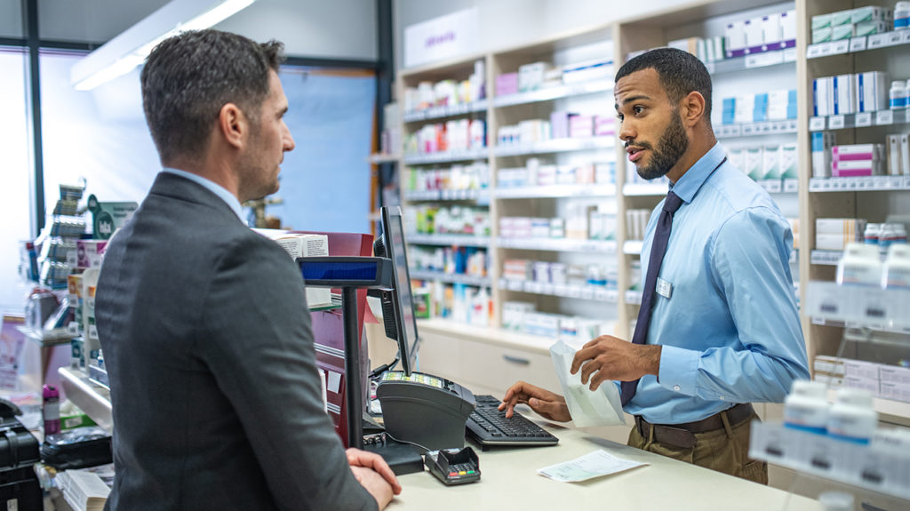 a man talking to a pharmacist about migraine medications