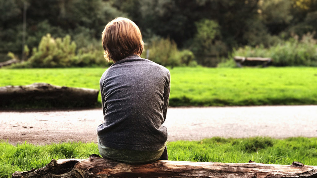 a child sat on a log and looking sad because he has experienced a number of adverse childhood experiences