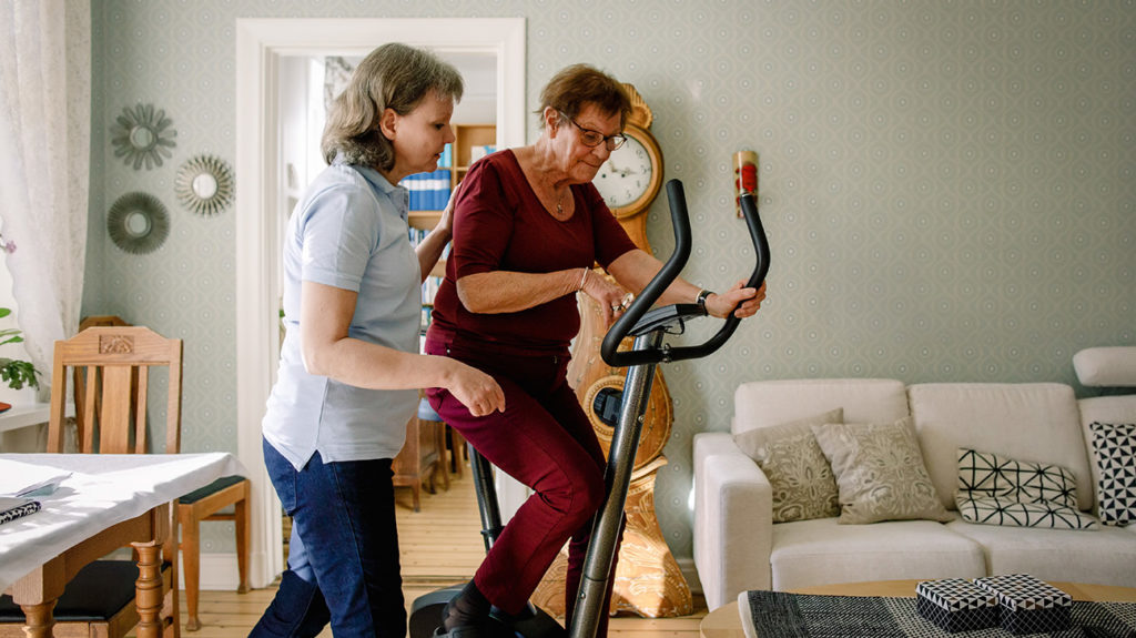 a senior woman on a exercise bike with a carer that she has to pay for herself as medicare does not cover long term care