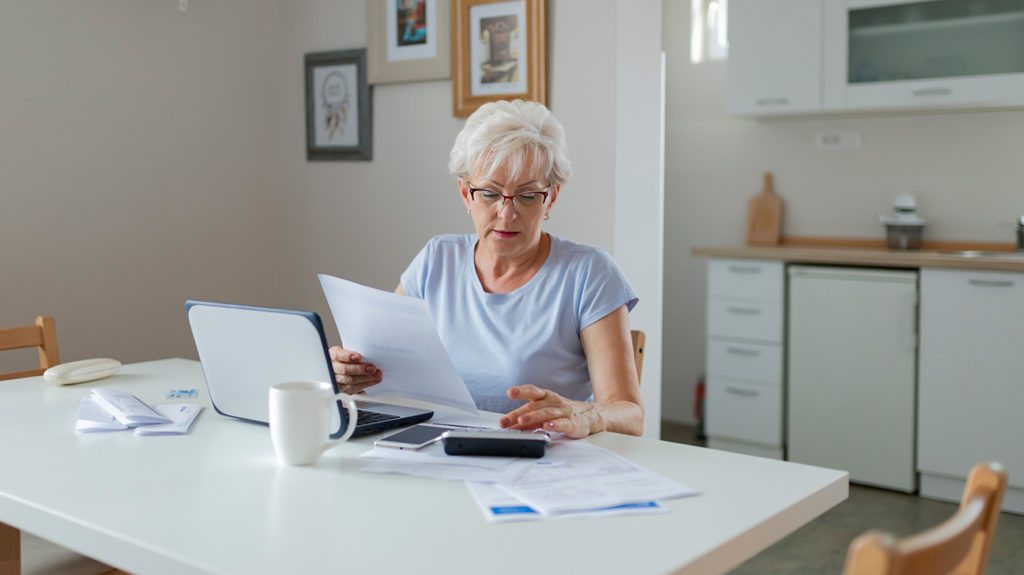a senior woman looking through paperwork to do with qmb medicare savings program