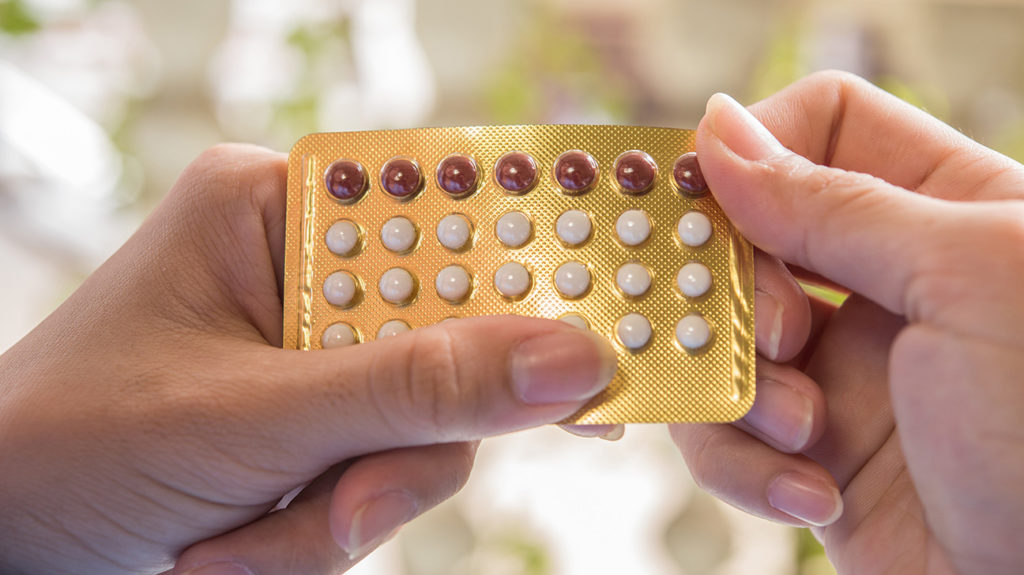 a woman holding a blister pack of birth control pills