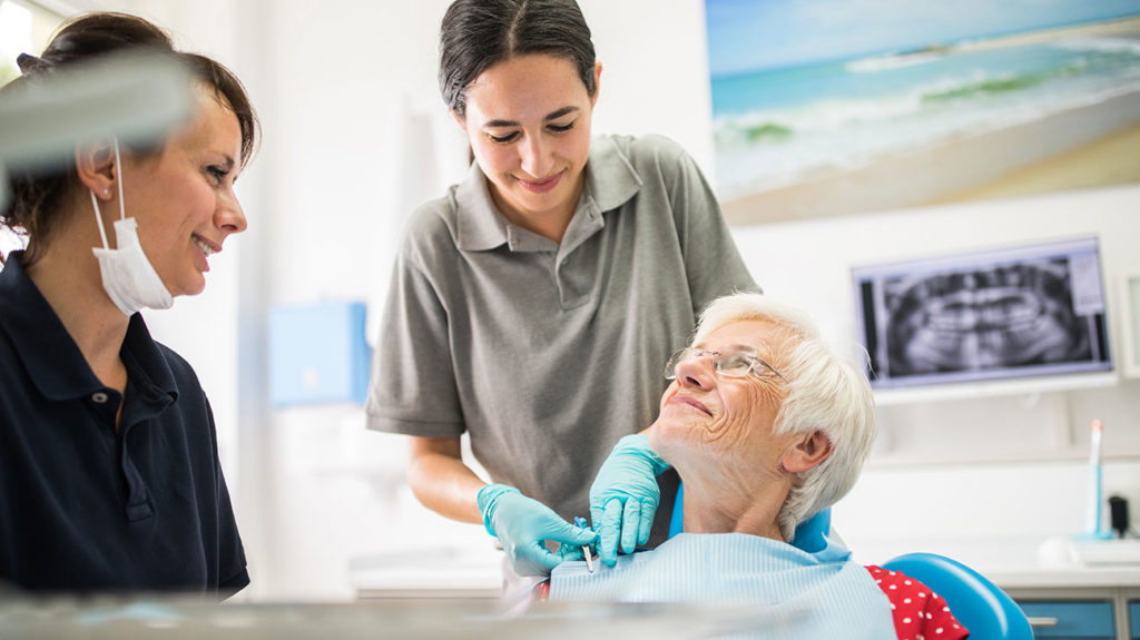 A senior sits ready for a dental procedure, after having spoken to her dentist about if Medicare does cover oral surgery.