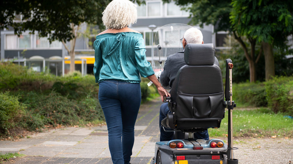 a daughter walking with her father who is in a electric wheelchair that was payed for by his medicare plan