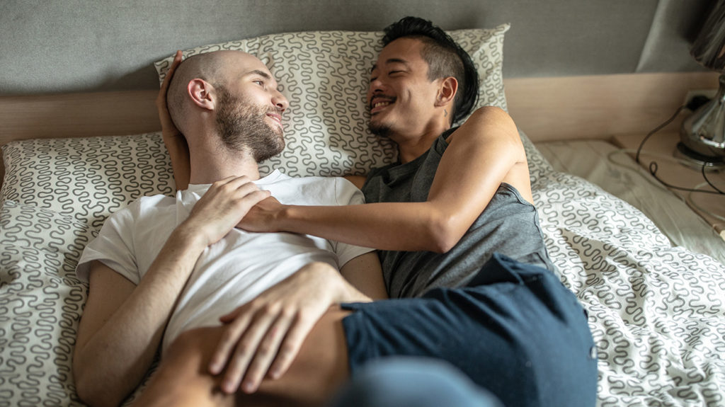 two men lying in bed together debating prostate milking
