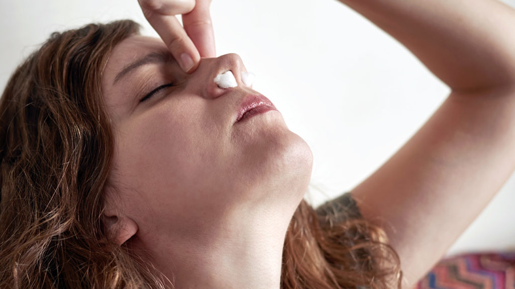 a woman holding her nose because she has a nose bleed which is one of the Weird early pregnancy symptoms