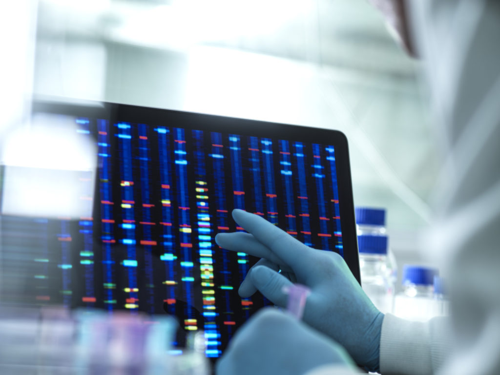 close up of scientist's gloved hand scrolling thorugh DNA structure on screen