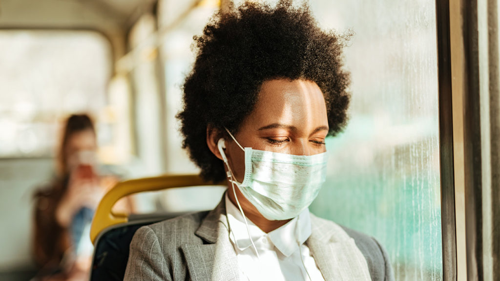 a woman on a bus wearing a surgical mask which is one of the types of facemasks a person can wear during a pandemic