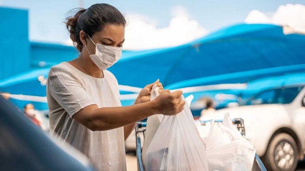 Une femme range ses provisions dans le coffre de sa voiture tout en portant un masque facial pour se protéger de la grippe.