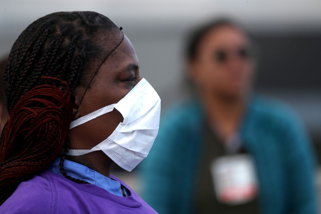 shot of a black woman in profile, health worker, wearing protective face mask