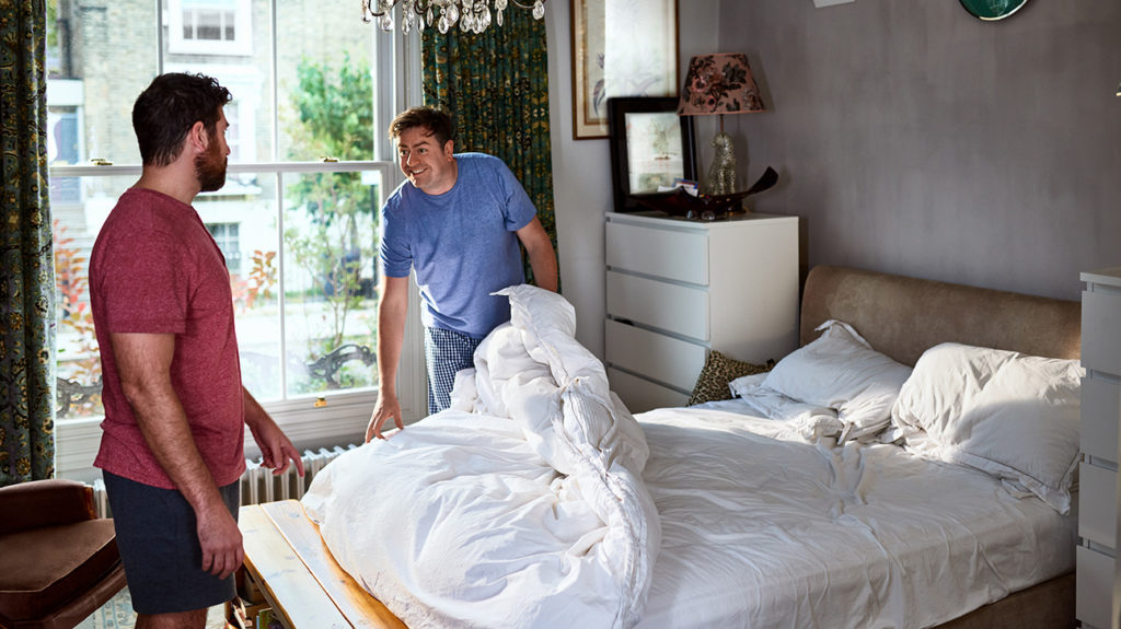 two men changing sheets on their bed as that is how to clean up after sex
