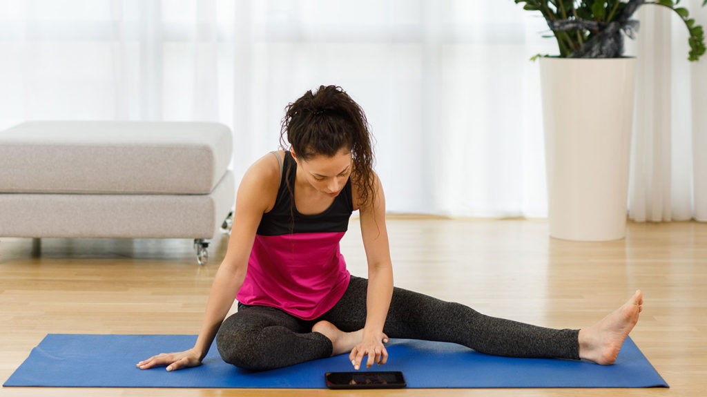A woman selects the best workout from a yoga app.