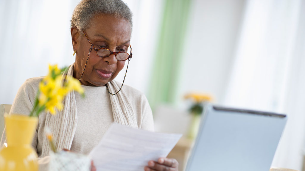 a senior woman looking at paper work to do with medicare supplement plan L