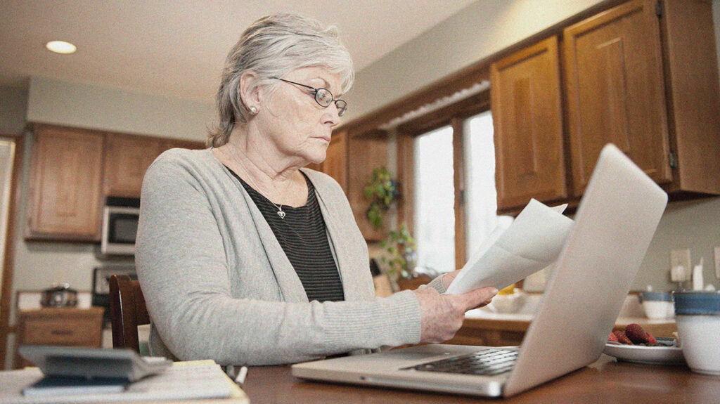 a senior woman looking at paperwork about the difference between medicare plans f and g