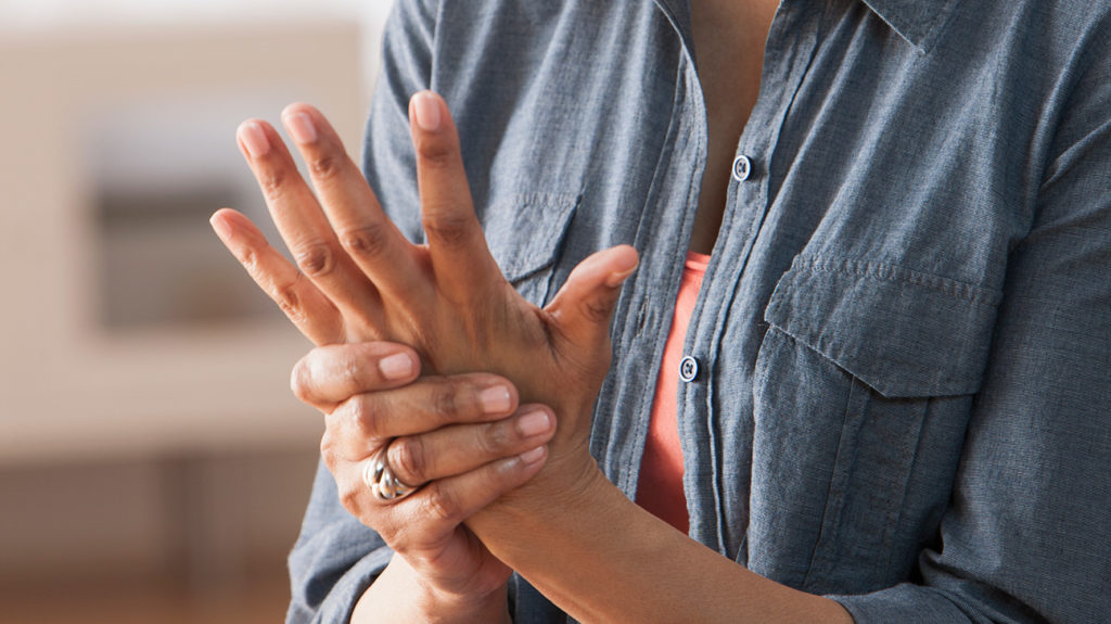 a woman holding her hand because she has pain there from Psoriatic arthritis