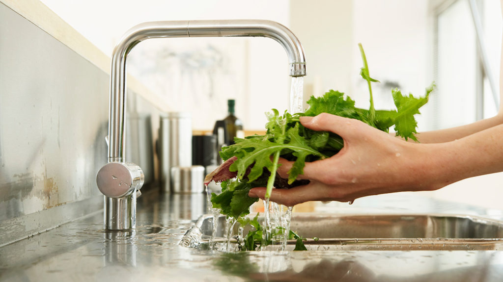 a person washing green vegetables under a tap which is one of the food rich in collagen