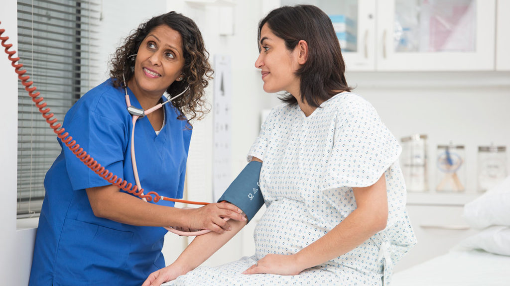 A nurse checks a pregnant woman's blood pressure to measure if she has a normal blood pressure in pregnancy.