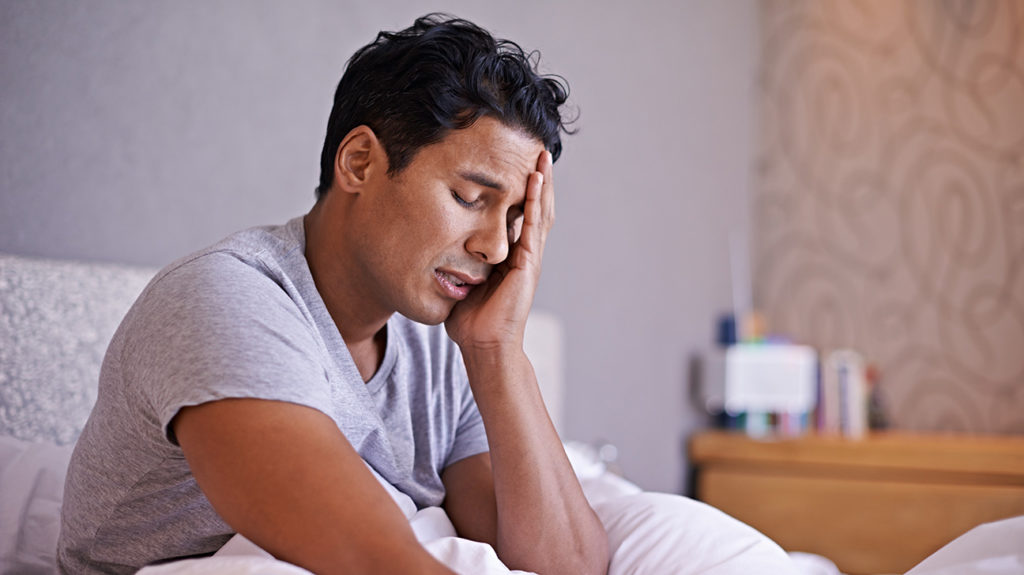 a man sat in bed experiencing an early morning headache