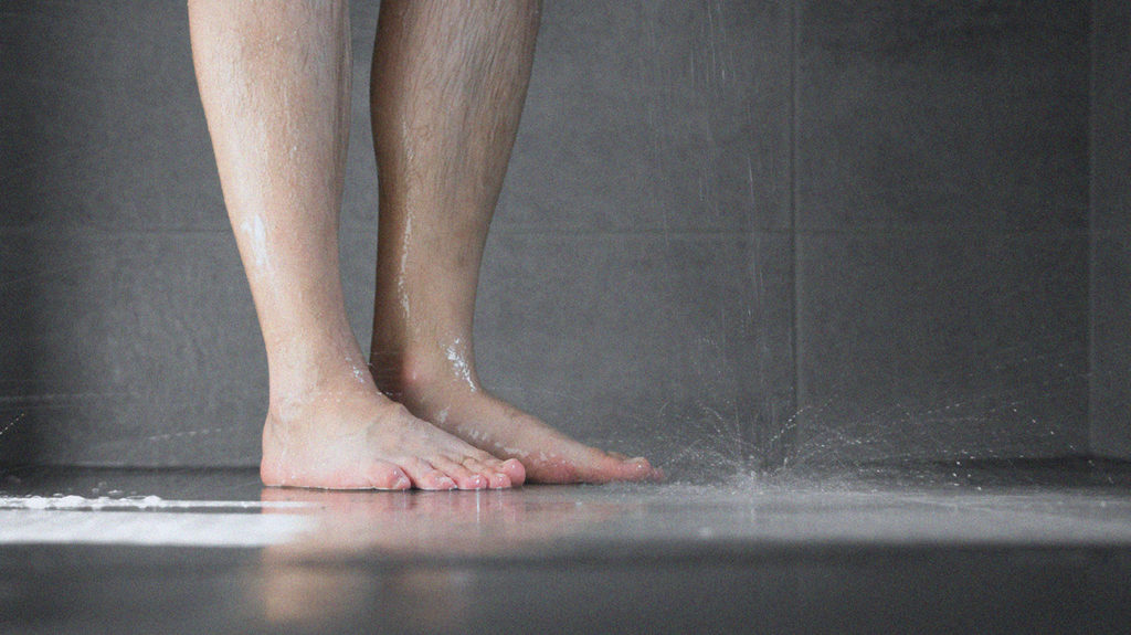 a man legs in the shower where he is washing himself to help with a itchy penis