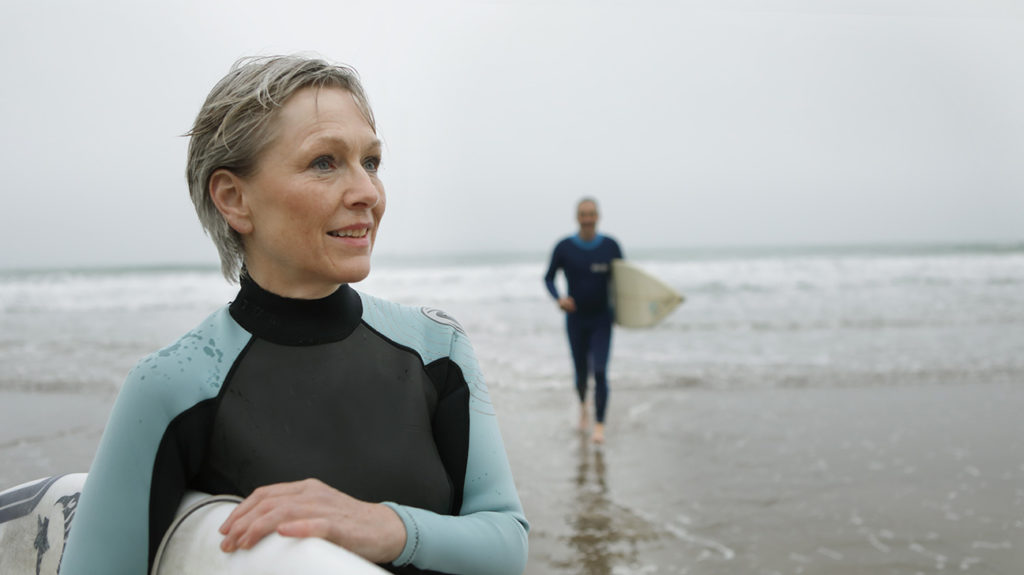 A senior couple on the beach together with surf boards during their retirement when they will be eligible for Medicare