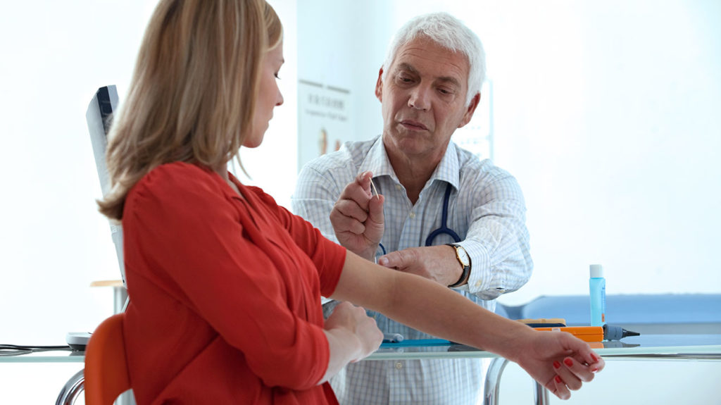 A woman consults with her doctor about a birth control implant.