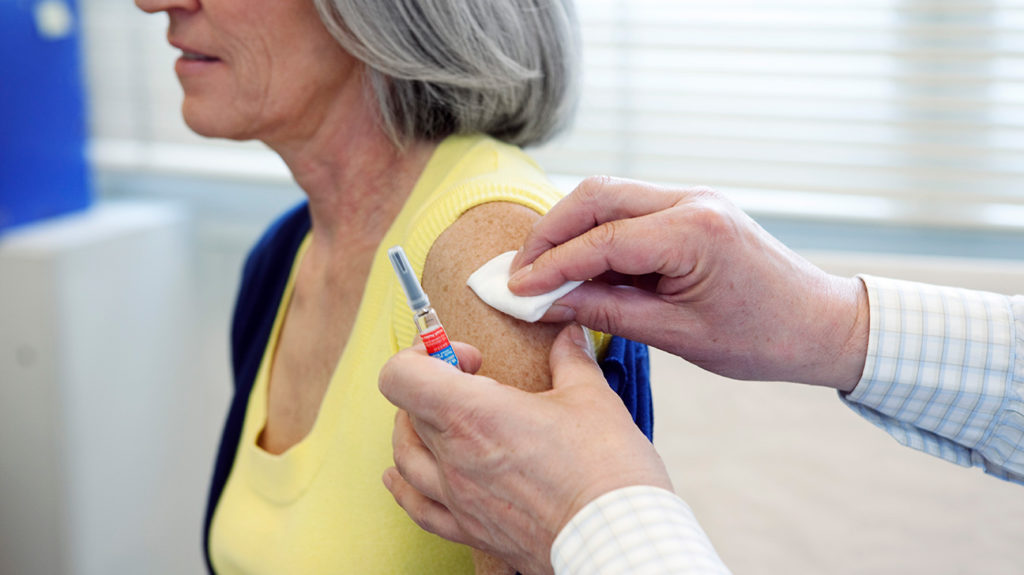 a senior woman having her armed prepared for a vaccine shot that she has coverage for with her Medicare plan