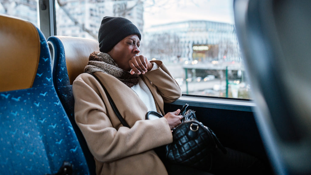 a woman on a bus yawning into her hand because she has fatique
