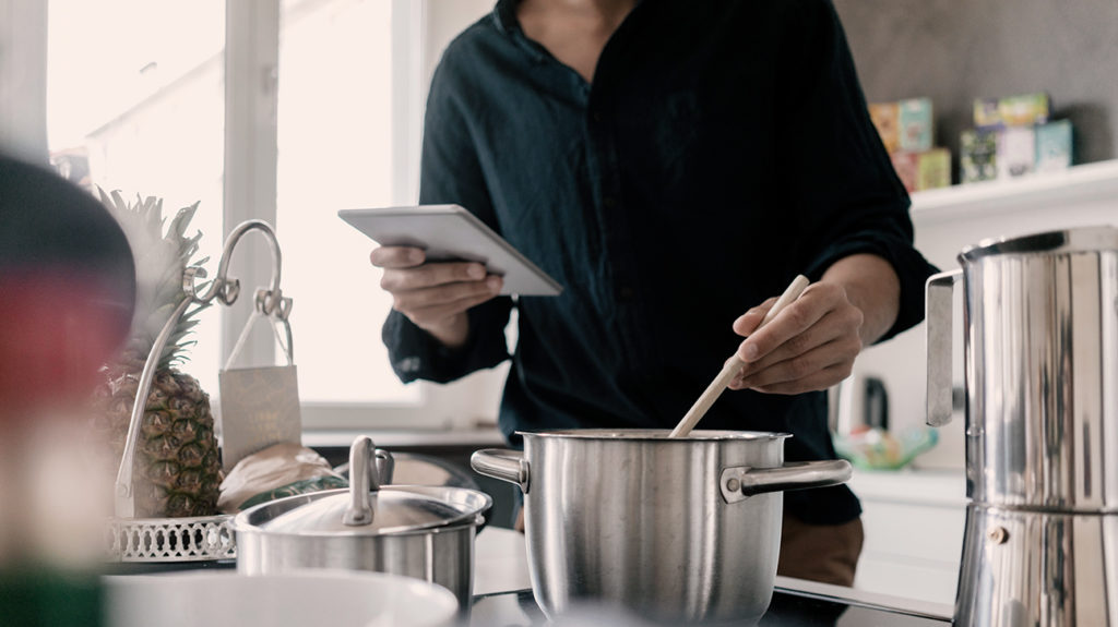a man cooking and looking at an app on his phone that will hopefully let him cook the best keto meal