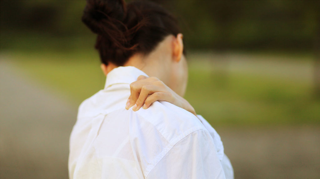 A woman clutches her shoulder due to chronic shoulder pain.