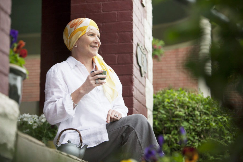 Woman with cancer smiling outside