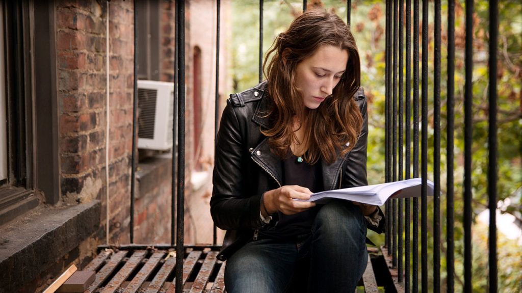 A woman reads on her fire escape as a way to adhere to the coronavirus tip of avoiding excessive news and social media.