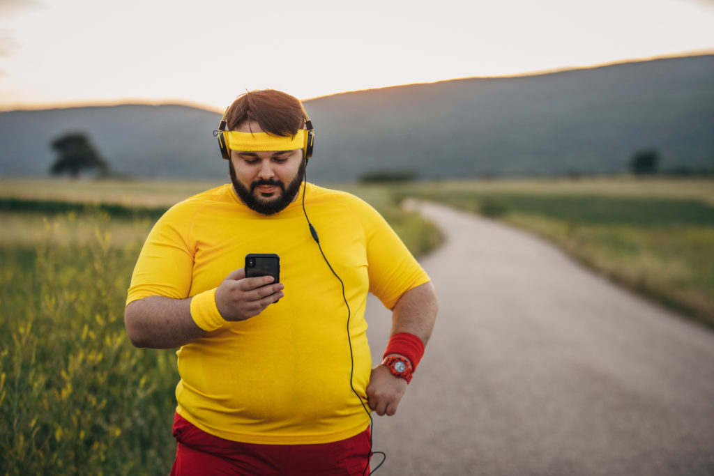 man with obesity in yellow top goes for a run and stops to check phone