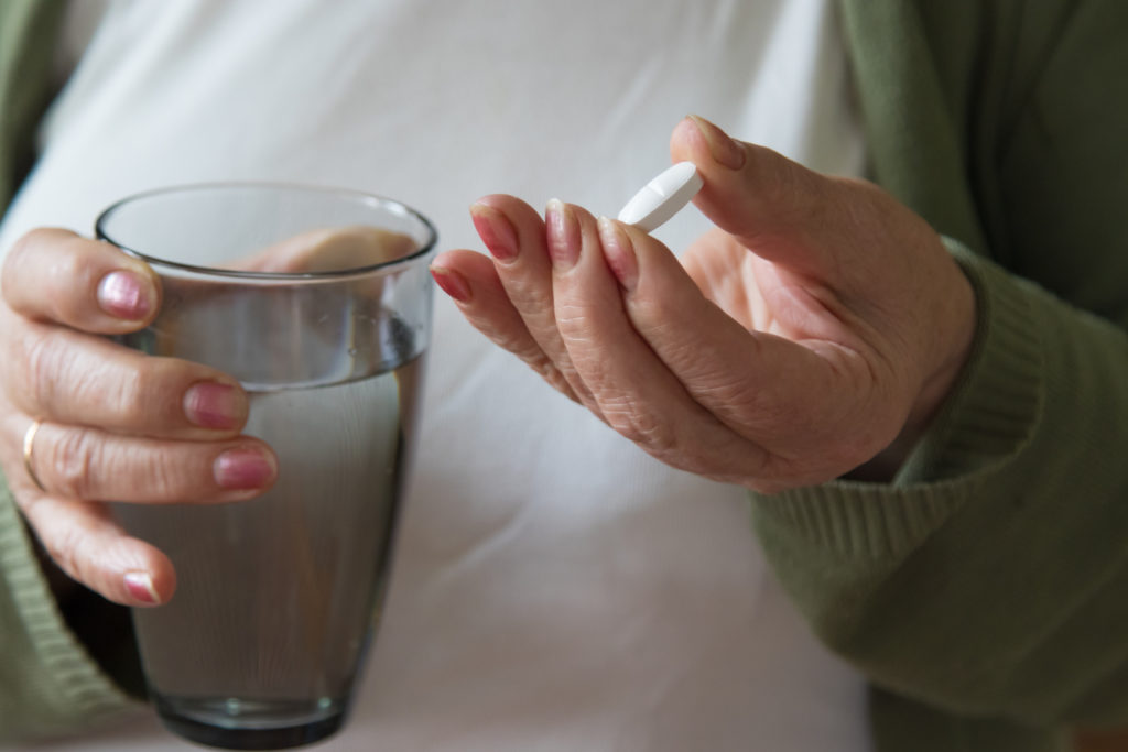 photo of hands holding a glass of water and a pill