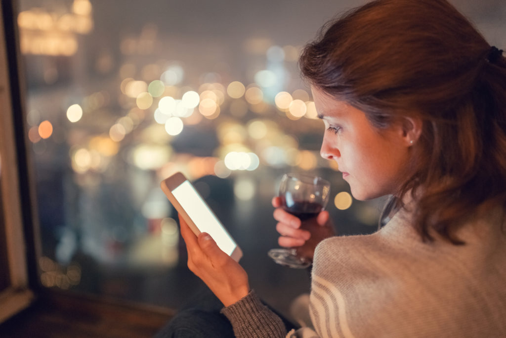 person holding glass of wine looking at smartphone