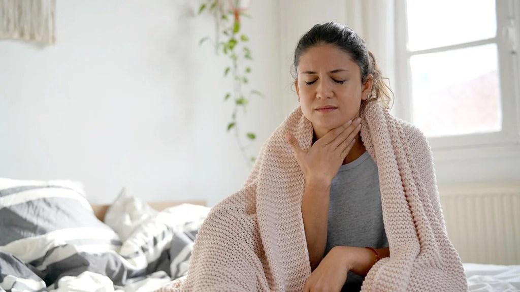 一个女人抱着她的喉咙,因为它疼痛,她不知道它会持续多久
