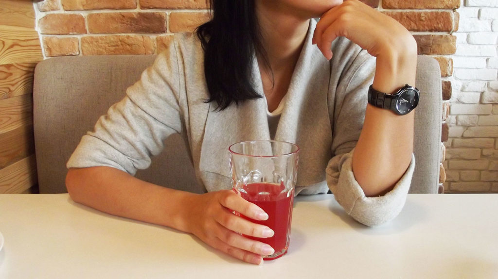 A woman drinks cranberry juice, which is one of the home remedies for UTIs.